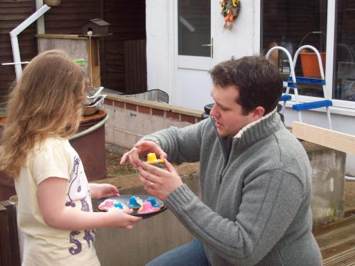 Jeany giving Uncle David an easter bonnet biscuit