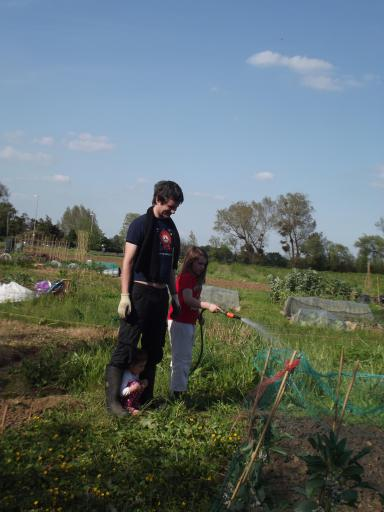 Alaric and Mary helping Jeany water the allotment