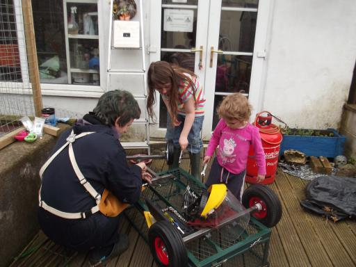 The girls helping daddy build a festival trolly