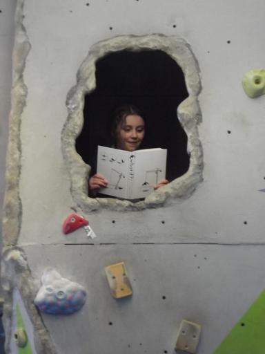 Close up of Jeany ready How It Works XKCD in the cave at the climbing wall for homework