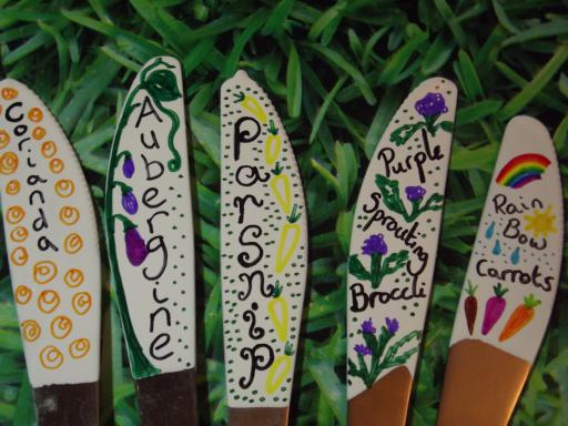 Close up of painted seed markers made of knives