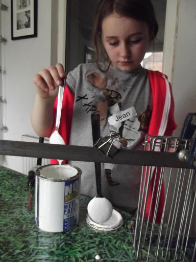 Jean dipping the spoons in the metal paint