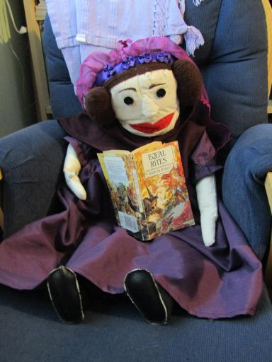 Ada Lovelace the puppet reading Equal Rites by Terry Pratchett