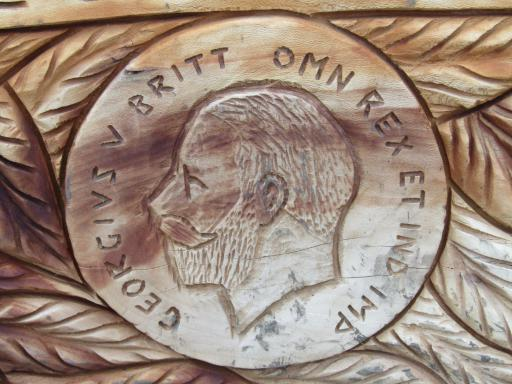 Close up of coin/medallion wood carving on bench